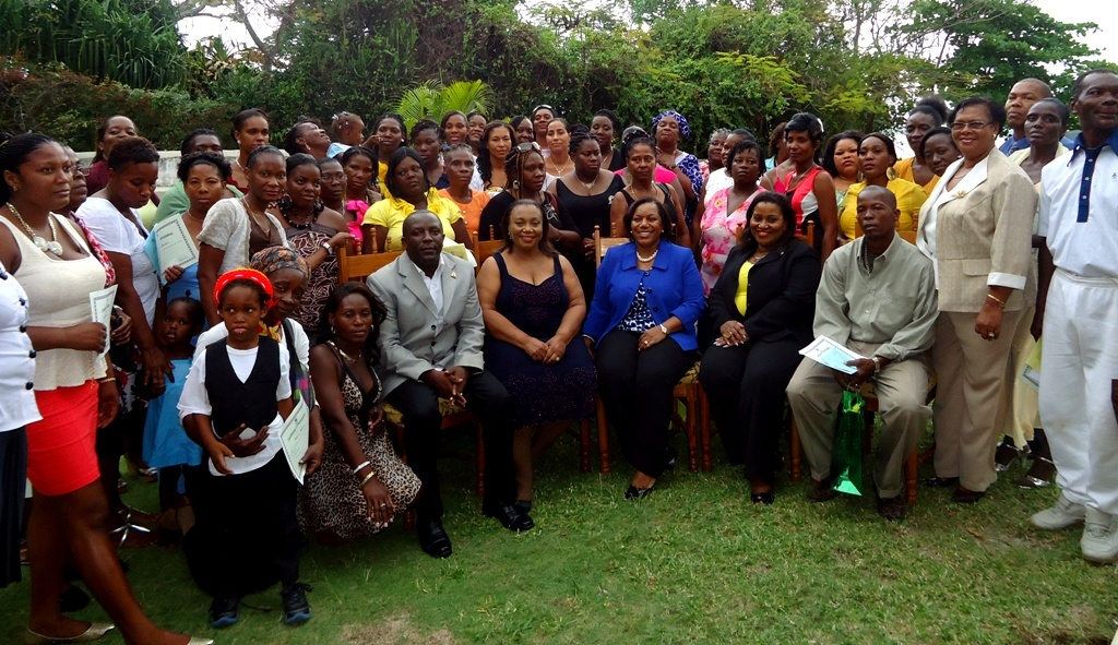 CDA's CEO Rosalee Gage-Grey (seated, centre); Director of Children and Family Programmes Audrey Budhi (seated, second left); Director of Financial Management and Accounting Services Michelle McIntosh (seated, second right), and other members of the Agency's Executive Management Team take time for a photo with some 69 parents who graduated recently from the Agency's parenting training programme.