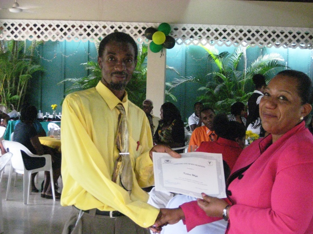 CDA's Director of Human Resource and Administration Rosalee Gage-Grey presents foster parent Devon Robinson with a certificate of appreciation at a recent function to honor parents from the South East Region (Kingston and St. Andrew; St. Catherine and St. Thomas at Tropical Elegance on Herb McKinley Drive, Kingston.