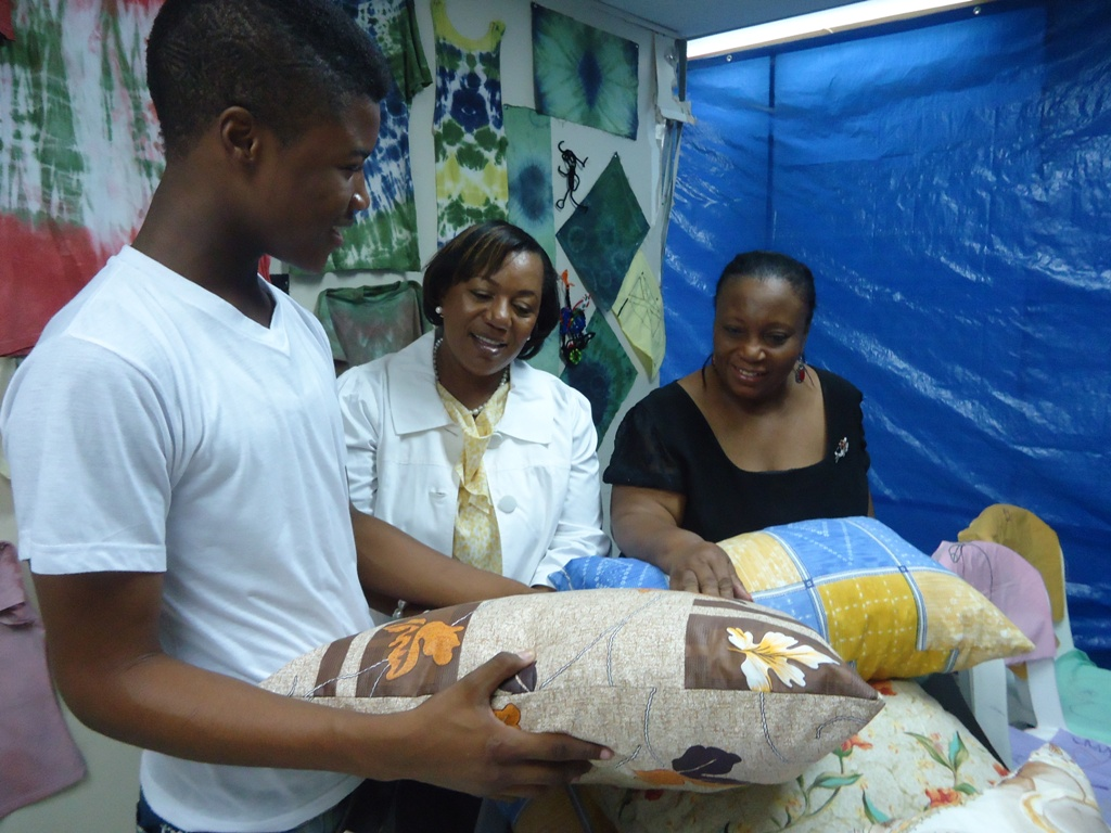 A young participant in the Child Development Agency's Children and Family Support Unit (CFSU) Summer Camp shows off the pillow he made to Acting CEO Mrs. Rosalee Gage-Grey (centre) and Director of Children and Family Programmes Audrey Budhi (right). The camp was held for 115 clients of the Agency at its 40 Duke Street location.