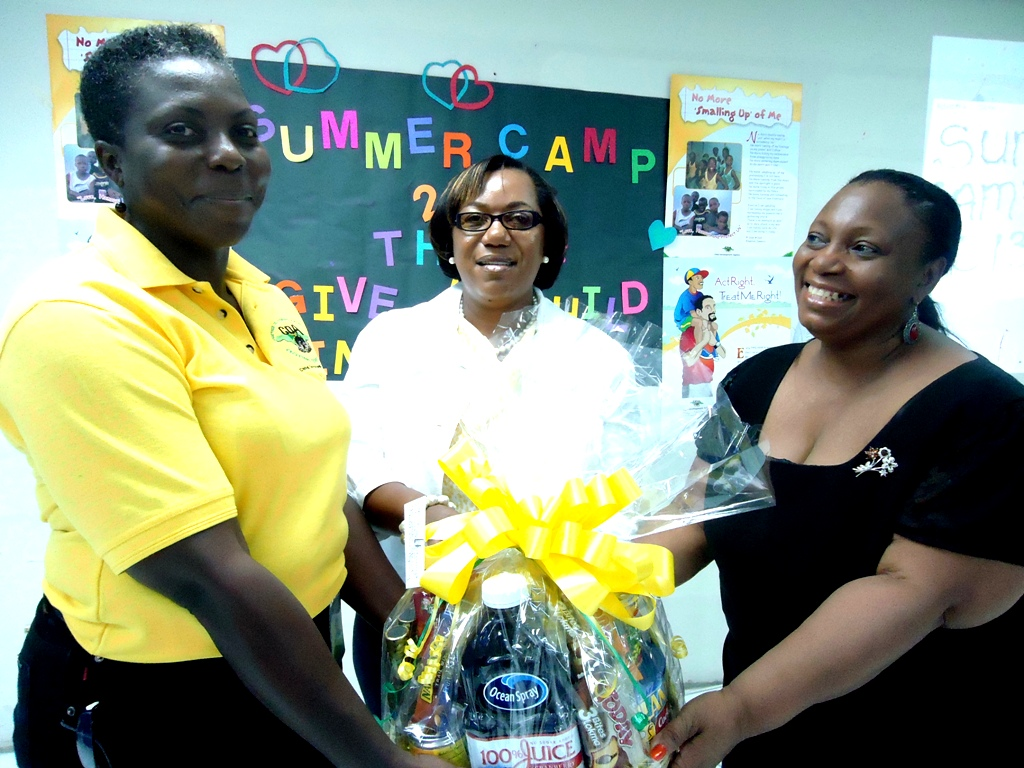 Job Well Done: Acting CEO Rosalee Gage-Grey (centre) and Director of Children and Family Programmes Audrey Budhi (right) present a gift basket to Head of CDA's Children and Family Support Unit Jean Duhaney for the work that was done in staging a summer camp for some 115 of its clients who hail from mainly the innercity.