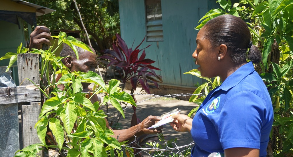 Child Development Agency Children's Officer, Julian Taylor (right) gives a St. Thomas resident information during a recent child sensitisation walk in Morant Bay and Bamboo River.