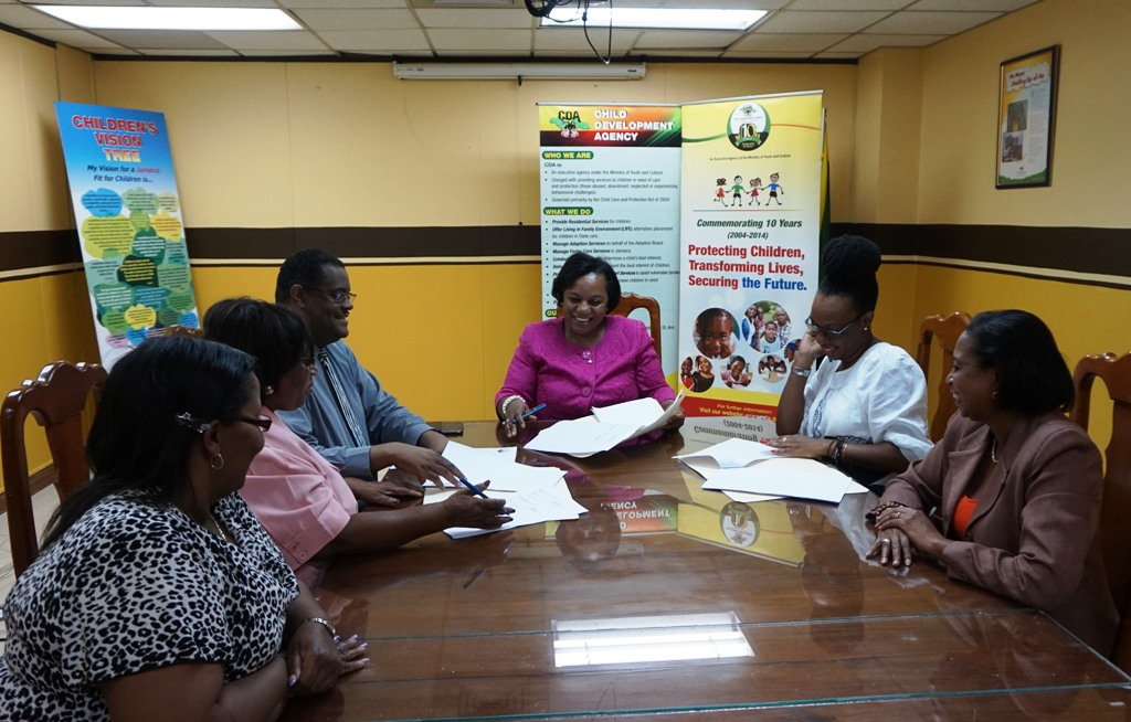 CEO of Child Development Agency Mrs. Rosalee Gage-Grey (centre) Executive Director of the Mico University College Youth Counseling, Resource Development Centre Dr. Claudine Hyatt (Mrs. Gage-Grey's immediate right) sign a Memorandum of Understanding for the Centre to assist the CDA with providing counselling services to children and staff. The signing took place at the CDA Head Office on Duke Street.  Other members of the CDA Executive Management Team participated in the signing. Left to Right are Director of Financial Management and Accounting Services Michelle McIntosh; Director of Children and Family Programmes Audrey Budhi; Director or Policy, Planning and Evaluation Newton Douglas, and Acting Director of Human Resource Management and Administration Marlene Gooden.