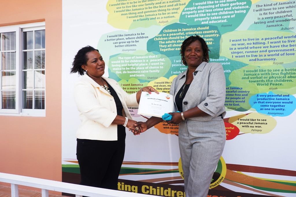CEO of the CDA Rosalee Gage-Grey presents a certificate to Regional Director for the Western Region Eunice Scott-Shaw signaling the plan to name the newly constructed counseling centre at the Granville Child Care Facility in her honor. The centre which is located in Carrick Foyle Trelawny is managed by the CDA was officially opened yesterday (June 24, 2015).