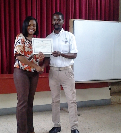 Children's Officer at the Child Development Agency's St. James Office, Raecine Hylton (left) presents a certificate of participation to parent Garnet Gillett (right) for taking part in a 20-hours parenting skills training course, organised by the Agency's Western Region. Some 87 parents who participated in the course were honoured for their effort at a recent graduation ceremony, held on (April 30) at the Calvary Baptist Church Hall, in Montego Bay, St. James. The course was geard at improving their parenting skills to cope with the challenges of child-rearing.