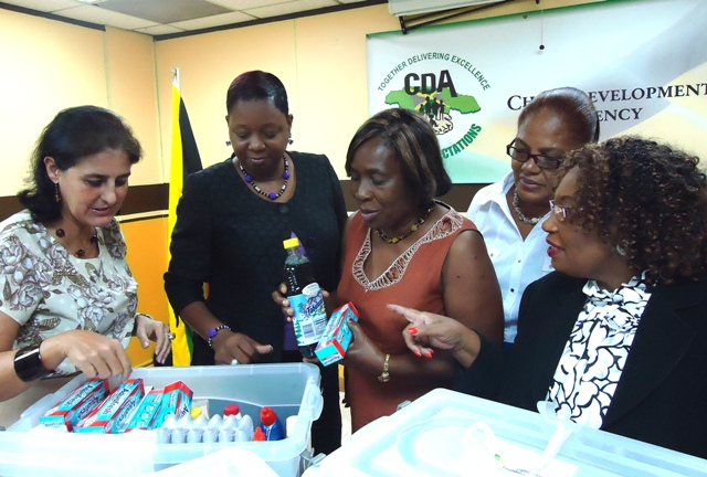 Spanish Ambassador to Jamaica Her Excellency Celsa Nuño (left) donates personal hygiene items and medical supplies on behalf or the Spanish-Jamaican Foundation, to eight government child care facilities. Here the Ambassador examines the container of products with CDA's CEO Carla Francis Edie (second right); Blossom Gardens Children's Home Facilities Manager Paola Genas-Brown; Interim Manager at Muirton Boys Home Esther McFarlane-Gooden,  and CDA's Director of Children and Family Programmes Audrey Budhi