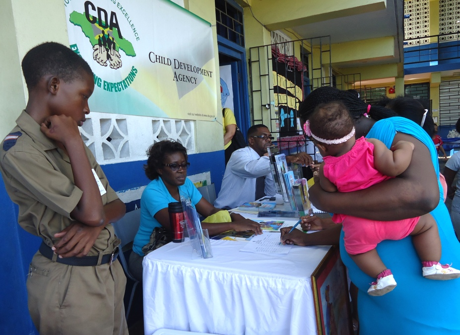 "Parents get information from Child Development Agency (CDA) officers at the Agency's booth while attending the Agency's Every Child is My Child Community Forum and Expo held at the Allman Town Primary School in Central Kingston recently. The event was held under the theme, ""Parenting for Positive Change in Jamaica""."