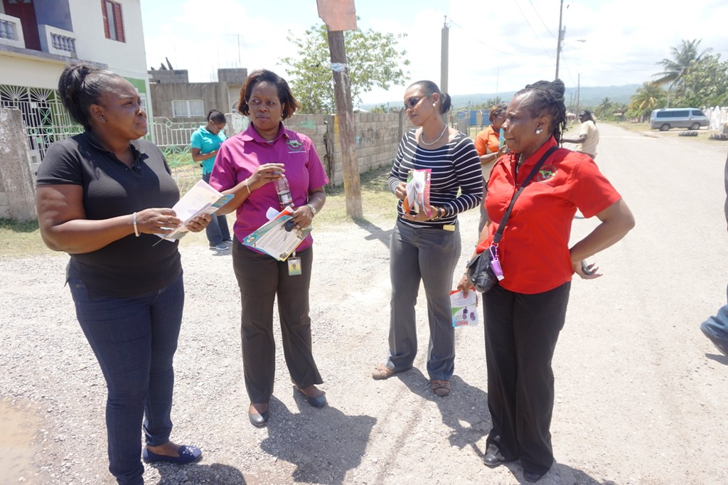 Child Development Agency Regional Director for the Southern Region Valerie Muhammad (right); Team leader Francine Rhoomes, and Children's Officer Kimberley Risden talk with Havannah Heights Police Youth Club Leader Melissa Burrell  as they discuss their next move during a child protection sensitisation tour of the Havanna Heights community in Clarendon yesterday (April 16).