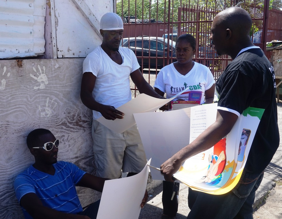A group of Taxi Operators in the Yallahs town gets information from the Child Development Agency's (CDA) Regional Director for South East, Robert Williams (right) and Children's Officer, Sasha Tucker (1st right) during the child abuse prevention and protection sensitisation walk on Friday (March 27).