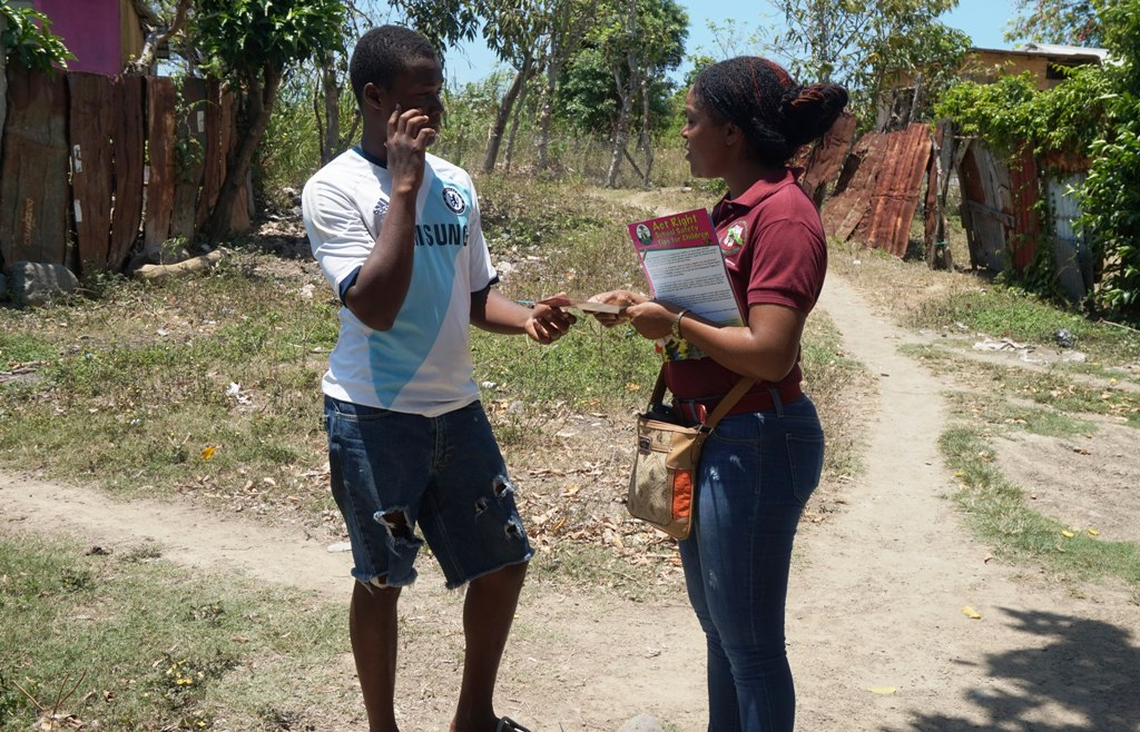 South East Region Children's Officer, Remona DaCosta (right) talks with a young man  in the Bamboo River community of St. Thomas during a child sensitisation walk recently.