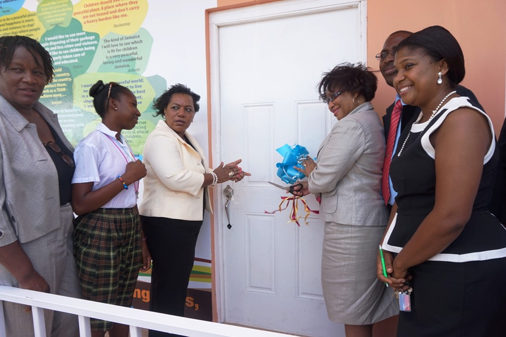 Senior Director in the Children's Affairs Division in the Ministry of Youth and Culture Grace-Ann Stewart McFarlane cuts the ribbon to officially open the Counselling Centre at the Granville Child Care Facility  yesterday (June 24, 2015)  as CEO of the CDA Rosalee Gage-Grey (third left) and Regional Director Eunice Scott-Shaw (left) look on.  Others from right include Kisha Shaw-Riley Manager at Granville, and His Worship the Mayor of Falmouth Councillor Garth Wilkinson.