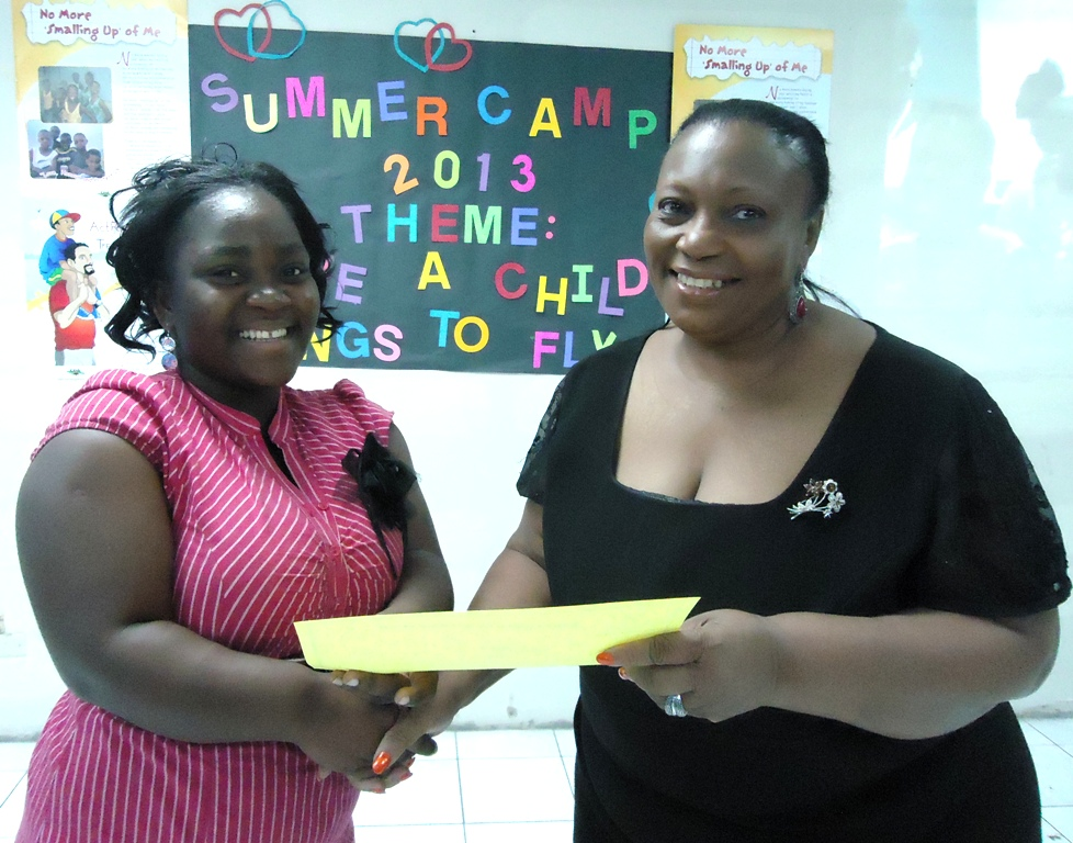 3.Member of the CDA's Children Advisory Panel Roshawna Byndloss (left) who volunteered at the Child Development Agency's three-week summer camp is presented with a certificate of appreciation by Director of Children and Family Programmes Audrey Budhi. The summer camp was held for 115 clients of the CDA's Children and Family Support Unit (CFSU) at the Agency's 40 Duke Street location.