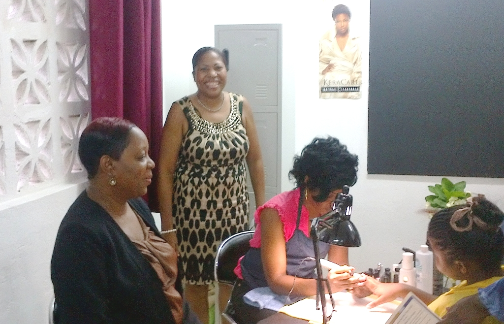 CEO of the CDA Carla Francis-Edie (seated) and Interim Manager of the Homestead Place of Safety Sophia Walters beam with pride as a ward of the home receives a manicure at the newly-opened Homestead Place of Safety Cosmetology Unit was officially opened at the Stony Hill Facility recently.   The facility was funded by the Inner Wheel Club of Kingston in partnership with the CDA.